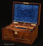 679JB: Antique Figured Rosewood box with lift-out compartmentalized tray and sprung drawer fitted for jewelry. There are mother of pearl escutcheons to the top and the front. There is a ruched velvet pad in the lid with mirror framed with gold embossed leather behind. It is released by pressing behind the lock catch. The sprung drawer is released by pressing on a button in the centre of the back facing. The lift-out tray is of mahogany construction with rosewood facings. New pads of velvet have been made to make the tray suitable for jewelry. There is further space beneath. Circa 1850.