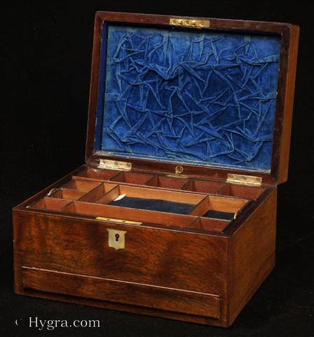 Antique Figured Rosewood box with lift-out compartmentalized tray and sprung drawer fitted for jewelry. There are mother of pearl escutcheons to the top and the front. There is a ruched velvet pad in the lid with mirror framed with gold embossed leather behind. It is released by pressing behind the lock catch. The sprung drawer is released by pressing on a button in the centre of the back facing. The lift-out tray is of mahogany construction with rosewood facings. New pads of velvet have been made to make the tray suitable for jewelry. There is further space beneath. Circa 1850.  Enlarge Picture