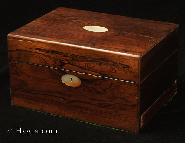 Antique Figured Rosewood box with lift-out compartmentalized tray and sprung drawer fitted for jewelry. There are mother of pearl escutcheons to the top and the front. There is a ruched velvet pad in the lid is framed with gold embossed leather behind. It is released by pressing behind the lock catch. The sprung drawer is released by removing a brass pin. The lift-out tray is of mahogany construction with rosewood facings. New pads of velvet have been made to make the tray suitable for jewelry. There is further space beneath. Circa 1840.  Enlarge Picture