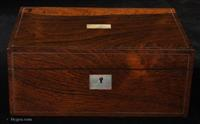 A figured  rosewood box , the grain on the front and top changing from dark brown to golden, giving an almost three dimensional quality. It has lines of white metal, a pewter alloy,  inlaid parallel and close to the sides.   The inside is lined with its original blue paper. There is lift-out tray with mitered beveled edge some of the divisions are missing. The layout would have been for cotton spools and sewing. The tray now has removable pads of blue velvet making the box suitable for jewelry or precious mementos.  There is a space under the tray, again lined with the manufacturer's paper.