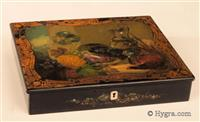 "Papier mâché writing box the top painted with a still life of fruit and game, framed  by gilded decoration. Inlays of mother of pearl are used to give a translucence to the painting. Th box is embossed to the base ""JENNENS & BETTRIDGE"".  The box opens to a sloping velvet covered writing surface and a lift out tray still covered in its original paper. The box has two original inkwells and a working lock and key. Circa 1830."
