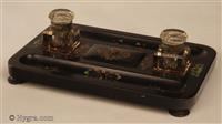 """Papier mâché inkstand impressed to the base """"JENNENS & BETTRIDGE BIRMm""""  beneath a Crown decorated in green red blue and gilt decoration, standing on turned feet. It has two period faceted glass inkwells with hinged tops."""