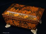 747SBJB: Shaped Regency penwork box decorated with stylised flowers and Chinoiserie scenes, depicting figures in exotic landscapes; some of the figures are European and some Oriental. It stands on period embossed gilded brass feet and also has period embossed brass ring handles. The original tray has been recovered.  Circa 1820.