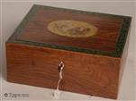 "729JB: Rosewood veneered box with a hand coloured print of a classical figure and edged with a paper print of oak leaves. The box is in the neoclassical tradition of the late 18th–early 19th century, which drew its inspiration from ancient art. Ladies dressed in diaphanous ""classical"" robes and posing as figures of classical mythology, were  thought to be the height of fashion at the time, with women such as Emma Hamilton (Lord Nelson's mistress) sporting such affectations for after-dinner entertainment."