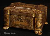 894TC: Chinese Export lacquer tea chest decorated with two colours of gold depicting scenes of Oriental life. The chest opens to two lift out pewter tea caddies or canisters. The caddy stands on gilded carved feet.  c1840