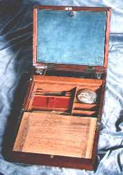 A combined writing box and dressing box of c1800. The top writing flap opens down to give access to grooming/shaving accessories. The lower flap has the conventional space for storing paper. The box is typical of the period made with solid mahogany reinforced with brass bindings. The brass binding protects the box from warping in changes of humidity. It also provides structural reinforcement for something expected to have a hard and useful life.