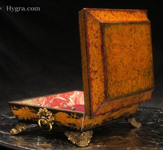 A rare Regency polychrome penwork box with tapering  sides and pyramid top standing on gilded embossed feet. The  colors are particularly rare. The  decorated in penwork,  depicts stylized representations of fantastical flowers and leaves. The penwork is within the tradition of fabric design which was popular during the 18th century. Such designs drew their inspiration both from eastern work and from European 16th and 17th century embroidery designs.  Enlarge Picture