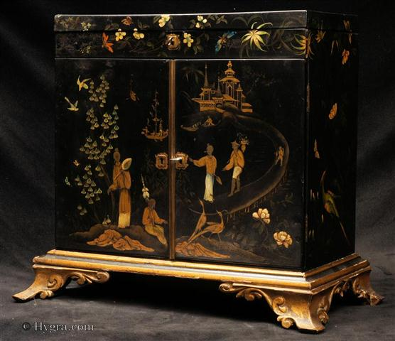Rare 18th C painted Papier Mâché table cabinet on gilded carved wooden stand. The two door cabinet with hinged top is decorated with chinoiserie themes on the outside and inside with wild flowers and butterflies. Enlarge Picture