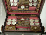 The top lifts to reveal a fully fitted sewing box. It has 8 mother of pearl spools, cut crystal scent bottle all set off with brocaded silk and gold  embossed  leather.  Enlarge Picture