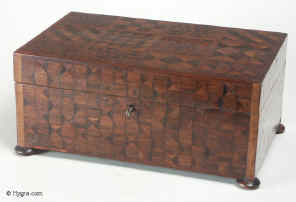 JB144: A refined Georgian box veneered with parquetry exploiting  subtle variations of wood color  and pattern. The woods are both native and imported hardwoods with some pieces  the added interest of end grain or oyster cut . The maker was exploring  geometry in wood and  may have been inspired by some of the mosaic inlay boxes being imported from India. There are different design on each side. The box stands on turned wooden feet has a working lock and key. Circa 1790.