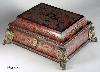 JB314: A shaped casket covered in boulle work of brass and red tortoiseshell, with guilt ormolu mounts and feet. The pattern is in bold swirls forming floral designs and cusps typical of 18th century work. The brass is engraved to give dimension to the design. The top is built around a stage where a musician sits playing his instrument. A complex composition, opulent and at the same time whimsical. The box is lined with silk. Circa 1750.