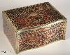 JB315: Boulle box in brass and red tortoiseshell having a serpentine front. and engraved brass and Boulle in red tortoiseshell depicting stylized scrolling  floral motifs to top sides and front.   The box is lined with silk and velvet. Circa 1840.