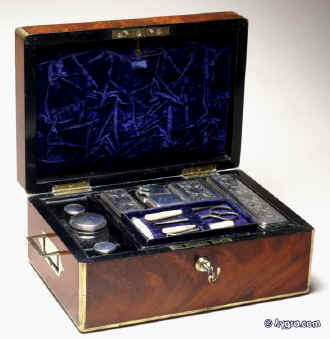 JB316: Brass edged flame mahogany fully fitted dressing box with inset brass handles and Bramah lock opening to a leather covered lift out tray with cut glass bottles with hallmarked silver tops (1827-9) a document wallet in the lid. Circa 1830. Enlarge Picture