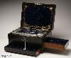 JB319: A fully fitted and intricate dressing box by C. Henry of Manchester in figured coromandel inlaid with engraved shield to the top and escutcheon in mother of pearl opening to a compartmentalized interior and retaining its original chased silver toped cut lead crystal jars and bottles by Thomas Whitehouse and having two sprung drawers fitted for jewelry. There is a liftout mirror with gold embossed mirror in the lid and a blind embossed leather document wallet behind. Circa 1860.