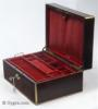 JB446: Figured rosewood and brass surround box circa 1830. A box veneered in figured rosewood box strengthened and accented with brass. The top central plaque bears initials in a stylized Gothic  script and a coronet,  probably of French nobility. There is also a brass inset of a lift-up aid on the front part of the lid. The box has extra support hinges on the sides which enable it to stay open at the same angle. The interior tray is original as is the silk faced 'envelope'. Additional velvet covers protect and render the interior more useable. Working key.