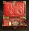 JB502 A brass bound mahogany gentleman's campaign  dressing box by D. Edwards, Holborn, London the compartmentalized interior with supplementary lids, all  lined with red embossed Morocco leather and containing steel boot-strap pullers pewter containers for ointments and shaving soap (P & R Hendri)  a bone shaving brush,  razors, and for sharpening ' ESTCOURT'S CRITERION STROP' Circa 1810.
