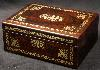 JB506: Rosewood box  with rounded edges, inlaid with brass to the front and top depicting stylized flora.  The design is controlled in deference to the Georgian neo-classical tradition but it also embraces the Regency influence of the Royal cabinet maker George Bullock, who introduced naturalistic elements to the earlier austere brass designs.  The inside of the box has been relined with hand marbled paper and velvet  and retains  its original lift out tray.  Circa 1825.