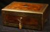 JB508: A very fine brass edged and inlaid  figured rosewood box ,  working Bramah lock, and having the Amorial crest for Fraser. The foliated borders are exceptionally well designed and executed with looping stems arranged in a mirror image fashion. The two sides of the pattern are separated by a palmette motif. The palmette is repeated as the central motif on the sides of the front of the box. The corners are inlaid with squared leaf designs. The severity of the lines, the arrangement of the design and the palmettes, are rooted in the neoclassical tradition.  The box has a compartmentalized leather and velvet lined interior with liftout tray. There is a hidden compartment with an unusual  secret release mechanism. The box also also has a drawer  fitted for jewelry which is secured shut by both a  brass pin and a lock. Circa 1820.