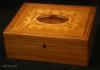 JB509: Inlaid maple Tunbridge ware box with a central book-matched medallion in burr yew, framed by  by a formal design of delicate foliage, suggesting the Grecian laurel or myrtle wreath and further framed by cross bandings. Inside the box  has a liftout tray with two supplementary lids also with inlay. The edges have an inlay in alternating maple and rosewood. Circa 1790.