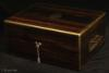 JB523:  Antique box veneered in strongly figured  coromandel,   by Hunt and Roskell, London. The box  has  brass edging,  central inlaid and engraved brass plaque, countersunk brass carrying handles, and a  working  Bramah lock with  key. The compartmentalized interior of the box is  also of very high quality.  It is lined in velvet and embossed leather and has a lift-out tray.  There is a document wallet in the lid. Circa 1870.