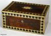 JB 163:  Antique Rosewood Box with Brass and Ebony Borders veneered in saw cut rosewood veneer and framed in a stylized inlaid border of ebony and brass; this box is characteristic of the elegant high quality of the Regency style.  It was made by the firm of Batley, who worked in Holborn, London, an area of bespoke cabinet makers. Circa 1820.