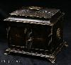 JB423: Antique Regency Table cabinet of architectural form the complex shape covered with embossed and tooled leather. The cabinet has double doors to the front which open to reveal a nest of drawers covered with tan colored leather. The cabinet stands on embossed  brass feet and has embossed brass ring handles. There is a secret compartment in the top. Circa 1820.