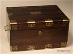 JB634: Figured rosewood box with rounded edges in alternating brass and rosewood having fine inlaid brass accents depicting stylized neo-classical motifs . The box is of high quality, which continues into the compartmentalized interior. There is a lockable side drawer of dovetail construction fitted for jewelry. It is lined in velvet and embossed leather. The box has its original leather covered lift-out tray. There is a document wallet in the lid with a mirror behind. Both the main lock and the drawer lock are working and have the same key. Circa 1825.
