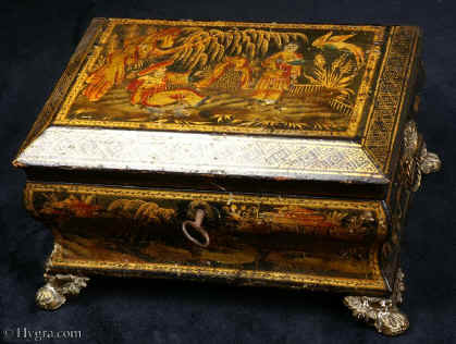 SB425:  Sewing box with  Japanned, raised and polychromed decoration on this sewing box depicting  a truly golden vision of Cathay. Figures relax in a garden with a distant rock in the background and the ho-ho bird above. This is a relatively late example of such work and it does not have an overall varnish. Note how the gold and the colors have remained brighter than in earlier examples. Circa 1820.