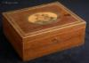 SB 493: A rare Georgian sewing box of rectangular form  edged with maple the top having a hand colored print depicting cherubs and framed with mitered purfling having a lift-out tray still retaining turned Tunbridge ware whitewood sewing tools. Circa 1800.