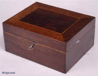 SB114: Antique sewing box veneered with mahogany, the top having a central panel of darker color framed by a mitered border of lighter color and contrasting figure, the inside being fitted for sewing with compartments for thread. Circa 1800.