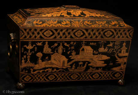 "A penwork tea chest, true to the spirit of the Regency. Its shape is of pure Egyptian inspiration. The top is decorated in designs of neoclassical derivation. The center features a pattera pattern slightly suggestive of a flower. The lower surround and the wide triangular panels feature acanthus leaves. The narrower sides have leaves enclosing either a stylized pinecone (ancient symbol of fertility) or a pineapple (a fruit of the East). The main body of work is in chinoiserie. The figures and landscapes have a light element, which was introduced in the second part of the 18th century, but which did not find true expression in England until the advent of penwork. Much of the design is inspired by Mathias Darly's and George Edwards' A New Book of Chinese Designs. For example, the book gives illustrations of ""Indian"" islands, bits of land somehow floating in the universe. Such islands were earthly manifestations of the ""Islands of the Blessed""."