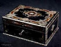 SB500: Antique opulent fully fitted sewing box in ebony profusely inlaid with tortoiseshell,  engraved brass, mother of pearl and abalone. The inside has  a silk covered lift out tray retaining a set of sewing tools  including turned and carved mother of pearl spools with matching tape measure and needle cleaner. A central tray has steel tools with tortoiseshell handles. Circa 1840.   Enlarge Picture